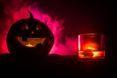 Halloween pumpkin with carved face and glass of whiskey with ice on a dark toned foggy background. Decorated. Selective focus