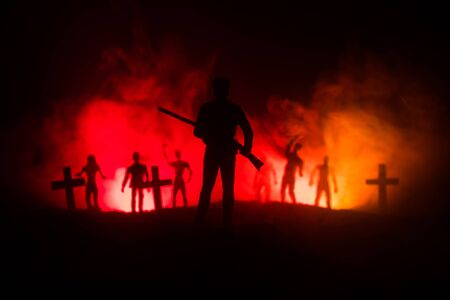 Man with riffle against zombie attack. Zombie apocalypse. Scary view of blurred zombies at cemetery and spooky cloudy sky with fog. Horror Halloween concept.