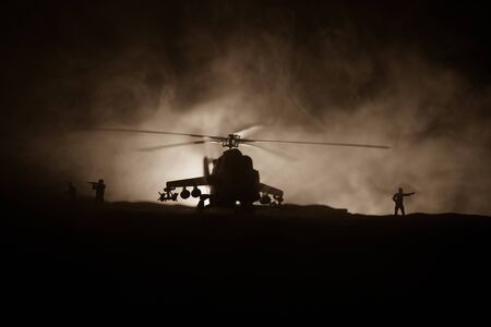 Silhouette of military helicopter ready to fly from conflict zone. Decorated night footage with helicopter starting in desert with foggy toned backlit. Selective focus. War concept Stock Photo