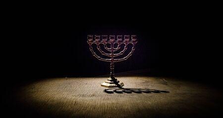 Low key image of jewish holiday Hanukkah background with menorah (traditional candelabra) on dark toned foggy background Stock Photo