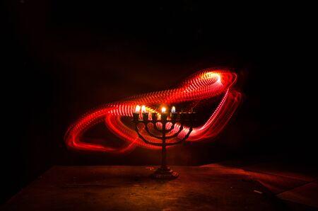 Low key image of jewish holiday Hanukkah background with menorah (traditional candelabra) on dark toned foggy background Imagens