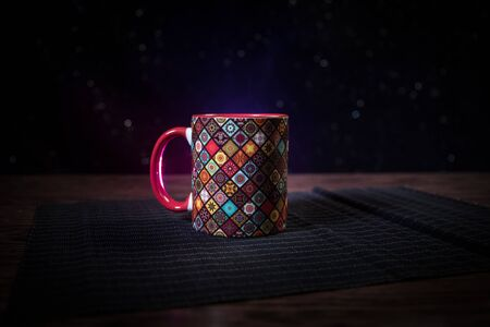 Beautiful eastern style textured ceramic cup of coffee (or tea) with smoke over dark toned background. Close up view. Imagens