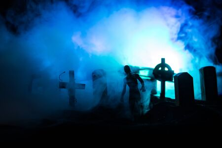 Scary view of zombies at cemetery dead tree, moon, church and spooky cloudy sky with fog, Horror Halloween concept with glowing pumpkin. Selective focus