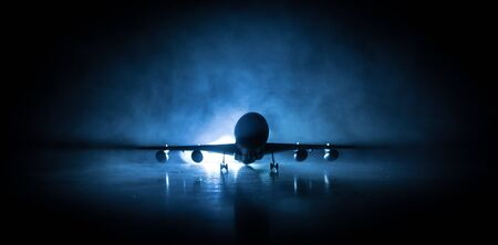 Artwork decoration. White passenger plane ready to taking off from airport runway. Silhouette of Aircraft during night time. Selective focus