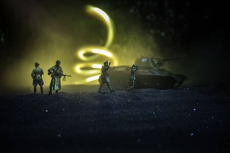 Battle scene. Military silhouettes fighting scene on war fog sky background. A German soldiers raised arms to surrender. Plastic toy soldiers with guns taking prisoner the enemy soldier. Artwork Stockfoto