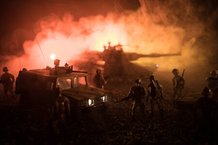 War Concept. Military silhouettes fighting scene on war foggy sky background at night. Armored vehicles with soldiers ready to attack. Artwork decoration. Selective focus