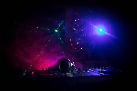 Dj mixer with headphones on dark nightclub background with Christmas tree New Year Eve. Close up view of New Year elements on a Dj table. Holiday party concept. Empty space Stock Photo