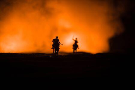 Reiter des Weltkriegsoffiziers (oder Kriegers) auf Pferd mit einem kampfbereiten Schwert und Soldaten auf einem dunklen nebligen Hintergrund. Schlachtfeld Schlachtfeld der kämpfenden Soldaten. Selektiver Fokus