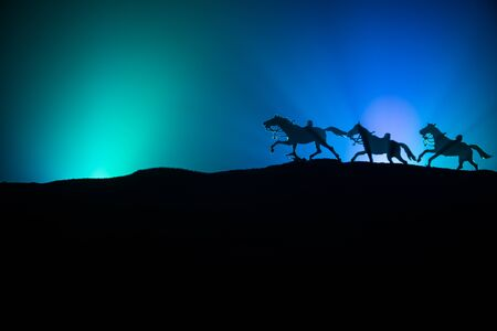 horse silhouette on the top of a hill against dark toned foggy background. Creative composition. War concept.