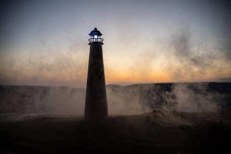 Faro con fascio di luce all'ora del tramonto. Vecchio faro in piedi sulla montagna. Decorazione della tavola. Messa a fuoco selettiva