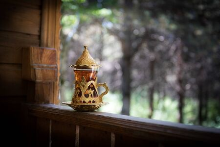 Eastern black tea in glass at the forest. Eastern tea concept. Armudu traditional cup. Green nature background. Selective focus