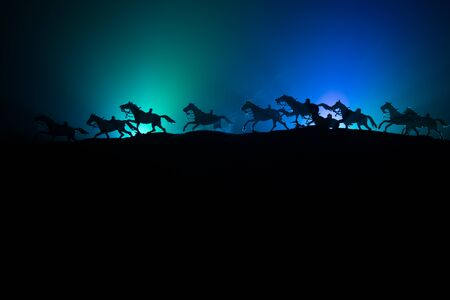 horse silhouette on the top of a hill against dark toned foggy background. Creative composition. War concept. Stockfoto