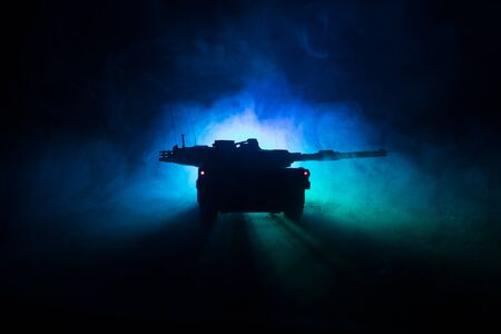 War Concept. Armored vehicle silhouette fighting scene on war foggy sky background at night. American tank ready to fight. Creative decoration Stockfoto