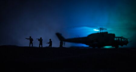 Silhouette of military helicopter ready to fly from conflict zone. Decorated night footage with helicopter starting in desert with foggy toned backlit. Selective focus. War concept Stockfoto
