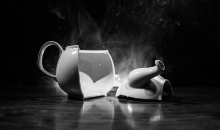 broken teapot on a dark toned foggy background. Pieces of ceramic teapot on wooden table. Selective focus