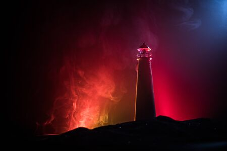 Lighthouse with light beam at night with fog. Old lighthouse standing on mountain. Table decoration. Toned background. Moonlighting. Selective focus Stockfoto - 131333971