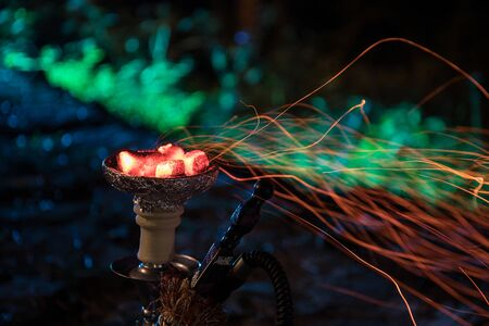 Hookah hot coals on shisha bowl with black background. Stylish oriental shisha at the forest during night time Stockfoto