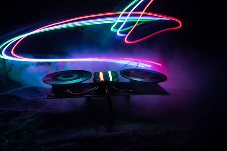 Dj club concept. Creative artwork decoration of dj table on dark toned background with lights and fog. Selective focus