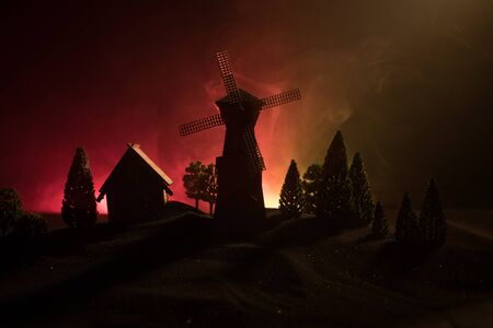 Windmill silhouette standing on hill against the night sky. Night decor with old windmill on hill with horror toned foggy background with light. Horror concept Banco de Imagens