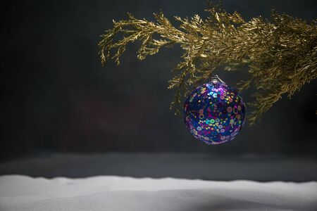 Christmas Decoration - bauble on branch of pine tree with holiday attributes on snow. Selective focus, bokeh background