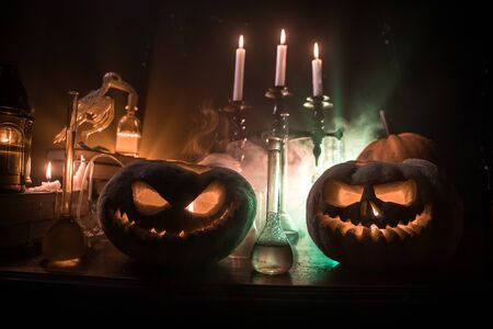 Wizard's Desk. Horror Halloween concept. Magic potions in bottles on wooden table with books and candles. Halloween still-life background with different elements on dark toned foggy background. Selective focus Stock Photo