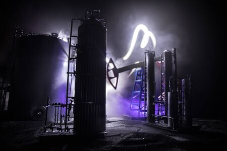 Oil pump and oil refining factory at night with fog and backlight. Energy industrial concept. Selective focus. Artwork decoration. 스톡 콘텐츠
