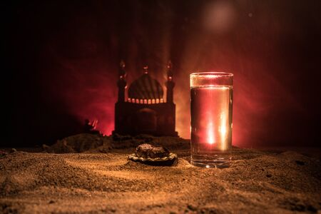 Water and dates. Iftar is the evening meal. View of decoration Ramadan Kareem holiday on sand. Festive greeting card, invitation for Muslim holiday. Selective focus