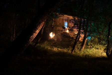 Horror Halloween concept. Burning old oil lamp in forest at night. Night scenery of a nightmare scene. Selective focus. Stok Fotoğraf