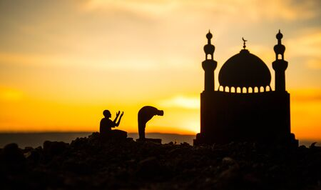 Concept of religion Islam. Silhouette of man praying on the background of a mosque at sunset. Festive greeting card, invintation for Muslim Holiday Stok Fotoğraf