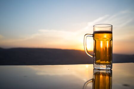 Glass of beer on a beach at sunset. Cooling summer drink concept. Close Up of A Glass of Draught Beer with the Bokeh of Sunlight Background, Soft Focus Stock Photo