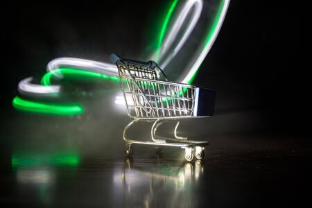 Empty shopping trolley on dark toned foggy background with some copy space. Financial crisis concept. Selective focus