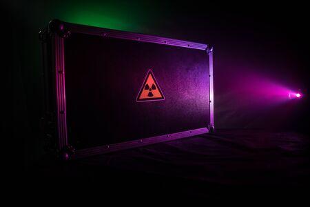 Radioactive (atomic ionizing radiation) danger warning symbol in triangular on a black case. Black suitcase with a sign of radiation hazard. Dark background. Stok Fotoğraf