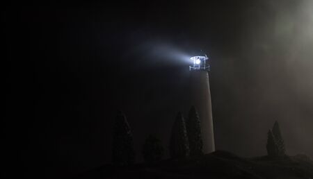 Lighthouse with light beam at night with fog. Old lighthouse standing on mountain. Table decoration. Toned background. Moonlighting. Selective focus