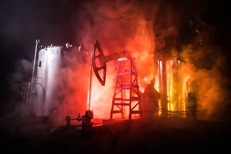 Oil pump and oil refining factory at night with fog and backlight. Energy industrial concept. Selective focus. Artwork decoration. Stok Fotoğraf