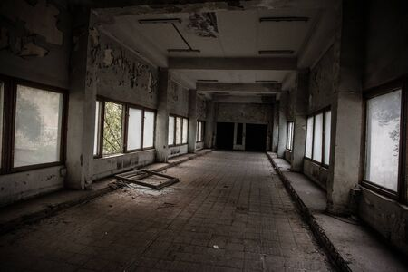 Dark, spooky tunnel, corridor with large windows at the end in abandoned soviet building.