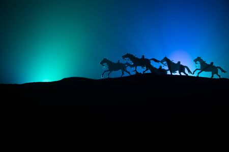 horse silhouette on the top of a hill against dark toned foggy background. Creative composition. War concept. Stok Fotoğraf