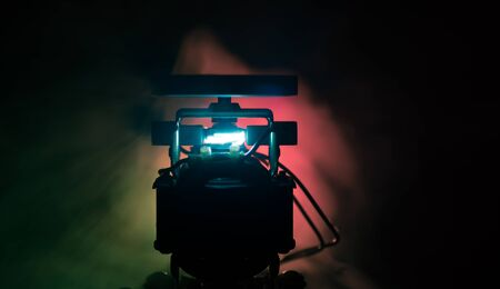 Old electric motor spinning on dark orange background. Broken motor burning and sparking. Industrial technology concept