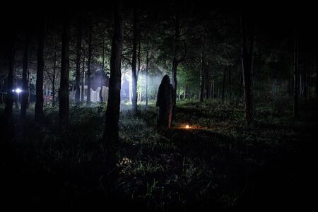 strange light in a dark forest at night. Silhouette of person standing in the dark forest with light. Horror halloween concept. strange silhouette in a dark spooky forest at night