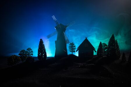 Windmill silhouette standing on hill against the night sky. Night decor with old windmill on hill with horror toned foggy background with light. Horror concept Stockfoto