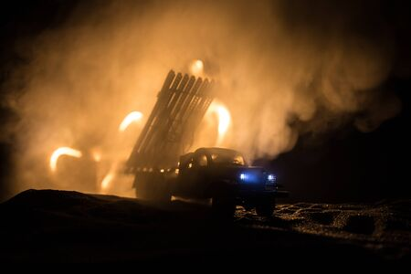 Rocket launch with fire clouds. Battle scene with rocket Missiles with Warhead Aimed at Gloomy Sky at night. Soviet rocket launcher on War Background. Creative composition.