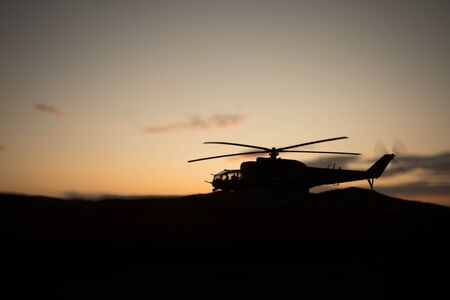 Silhouette of military helicopter ready to fly from conflict zone. Decorated night footage with helicopter starting in desert with foggy toned backlit. Selective focus. War concept Stock fotó