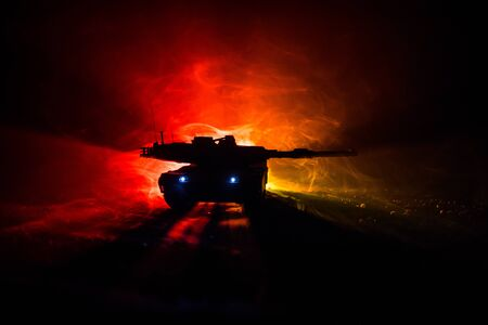 War Concept. Armored vehicle silhouette fighting scene on war foggy sky background at night. American tank ready to fight. Creative decoration 版權商用圖片