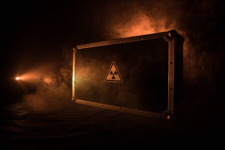 Radioactive (atomic ionizing radiation) danger warning symbol in triangular on a black case. Black suitcase with a sign of radiation hazard. Dark background. Banque d'images - 133780912