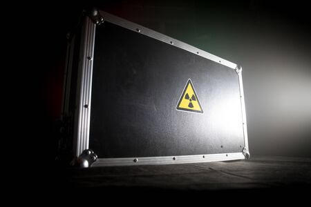 Radioactive (atomic ionizing radiation) danger warning symbol in triangular on a black case. Black suitcase with a sign of radiation hazard. Dark background. Stock fotó