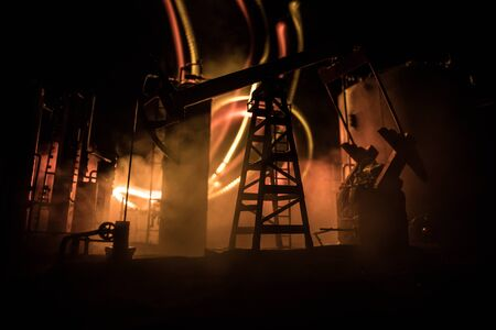 Oil pump and oil refining factory at night with fog and backlight. Energy industrial concept. Selective focus. Artwork decoration. Reklamní fotografie