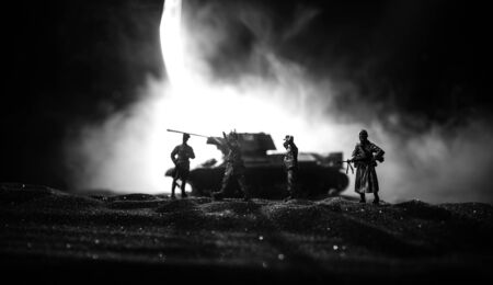 Battle scene. Military silhouettes fighting scene on war fog sky background. A German soldiers raised arms to surrender. Plastic toy soldiers with guns taking prisoner the enemy soldier. Artwork 版權商用圖片