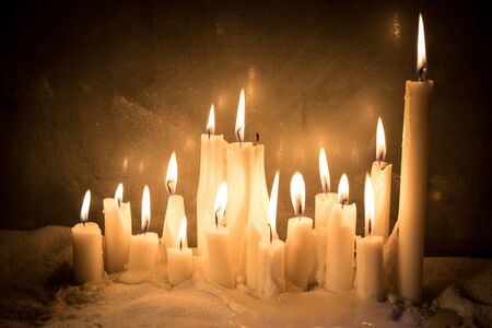 Candles in night on snow. Creative artwork decoration. Selective focus. Empty space for your text Reklamní fotografie