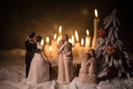 Winter holidays and love concept. Couple doll figures and Christmas decorations on snow with many candles on background. Empty space for your text Reklamní fotografie
