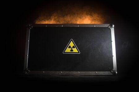 Radioactive (atomic ionizing radiation) danger warning symbol in triangular on a black case. Black suitcase with a sign of radiation hazard. Dark background.