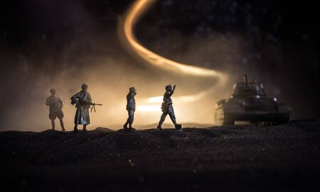 Battle scene. Military silhouettes fighting scene on war fog sky background. A German soldiers raised arms to surrender. Plastic toy soldiers with guns taking prisoner the enemy soldier. Artwork Archivio Fotografico - 134749087
